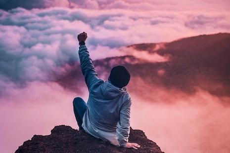 junger Mann sitzt auf der Spitze eines Berges und hat sein Ziel erreicht ist stolz und erfolgreich